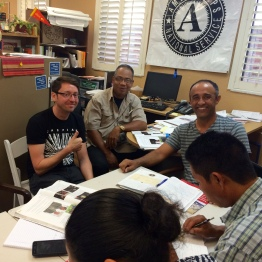 UCF student, Ricky, sits with HCC students, Rubén and Albeiro. They have finished their activity and are looking at the camera. Ricky is giving a thumbs up to the camera.