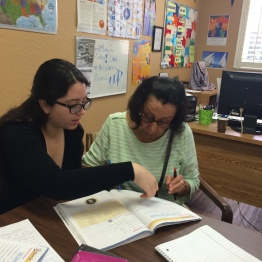 This is a photo of UCF student Esther and HCC student María Paz working from our wowkbook. Esther wears black glasses and has long, curly hair. María Paz wears black glasses and has short hair.