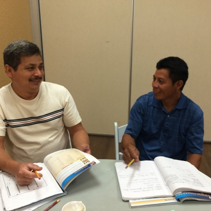 HCC students, Silvino and Edgar review their work during break.